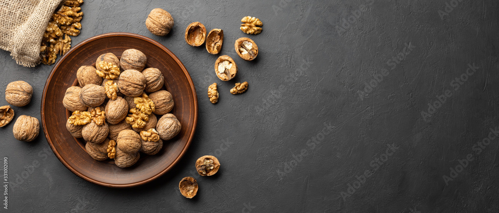 Fototapeta Nuts. Walnut kernels and whole walnuts on dark stone table. Black background. Top view, flat lay with copy space.