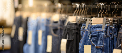 Fototapeta Jeans or Denim pants (trousers) hanging on rack in clothes shop. Fashion product collection in clothing store for selling. Textile industry and business concept obraz
