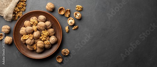 Obraz Nuts. Walnut kernels and whole walnuts on dark stone table. Black background. Top view, flat lay with copy space. - fototapety do salonu