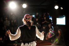 A Selective Focus View From Behind An Actor Dressed In Pirate Costume, Performing On Stage To A Crowd Of Onlookers With Blurry Spot Lights And Copy Space.