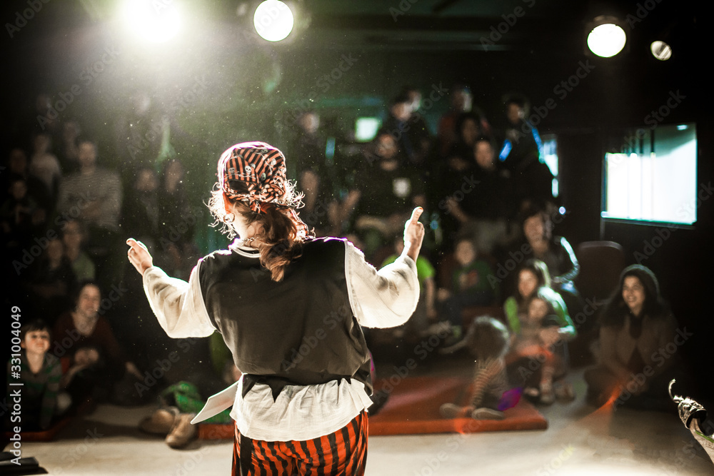 Fototapeta A performing arts entertainer is seen from the back in selective focus, dressed as a pirate on stage during a comedy act with blurry audience at back.