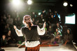 Leinwanddruck Bild - A performing arts entertainer is seen from the back in selective focus, dressed as a pirate on stage during a comedy act with blurry audience at back.