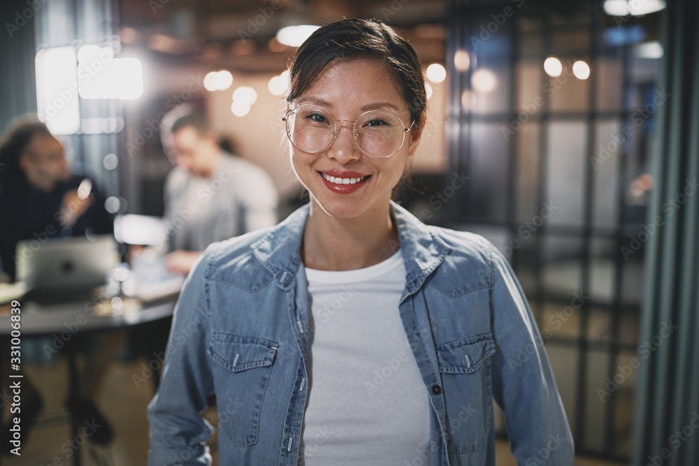 Fototapeta Asian businesswoman smiling with colleagues working in the backg