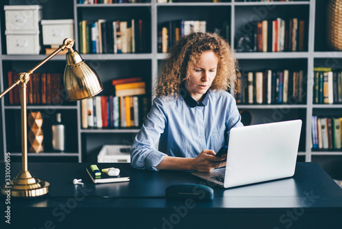 Concentrated young woman sitting at desk in library and working on laptop and phone from home Fototapet