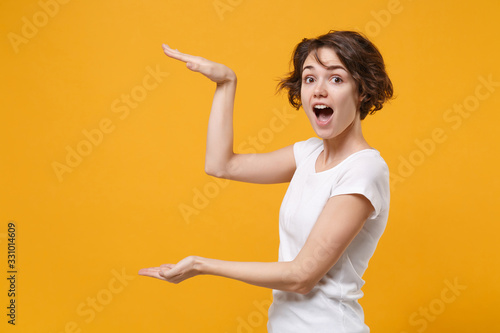 Cuadros en Lienzo Shocked young brunette woman in white t-shirt posing isolated on yellow orange background in studio