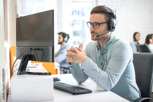 Fototapeta Customer service support operator man with headphones and microphone listening t