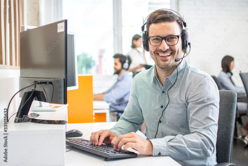 Fototapeta Male customer support phone operator with headset working in call centre. Group of sales agent working in office.