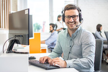 Male Customer Support Phone Operator With Headset Working In Call Centre. Group Of Sales Agent Working In Office.