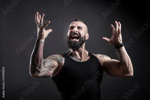 Uomo tatuato con barba urla arrabbiato , isolato su sfondo nero Wallpaper Mural