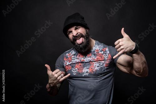 Fényképezés Uomo con barba fa gesto da Hippy con le mani e fà la lingua , isolato su sfondo
