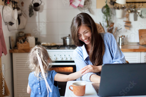 Obraz Working mom works from home with kid. Happy mother and daughter have fun. Successful woman and cute child using laptop. Freelancer workplace in kitchen. Female business. Lifestyle authentic moment - fototapety do salonu