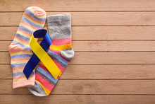 World Down Syndrome Day Background. Down Syndrome Awareness Concept. Socks And Ribbon On Wooden Background