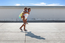 Smiling Young Girl Giving Piggy Back Ride To Her Little Sister In Urban Environment