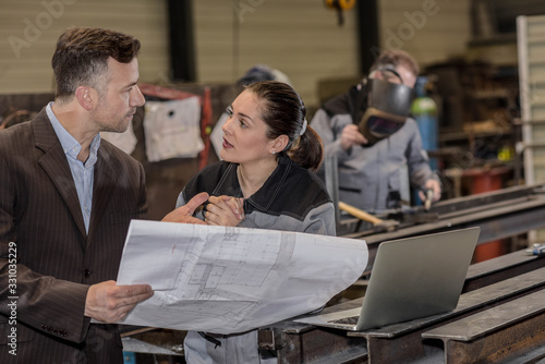 The factory owner is giving orders to his female worker Canvas Print