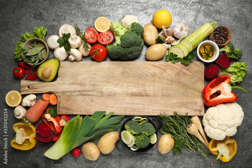 Fototapeta Fresh products and wooden board with space for text on grey table, flat lay. Healthy cooking