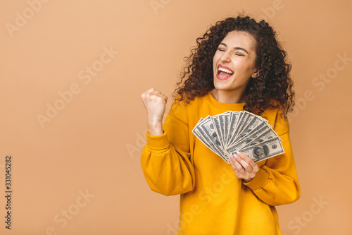 Obraz na plátně Portrait of a cheerful young woman holding money banknotes and celebrating isolated over beige background