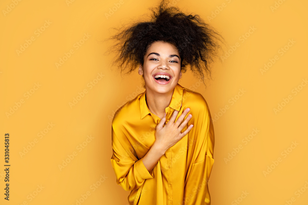 Fototapeta Overjoyed girl holds her hand on heart, can't stopping laughing. Photo of african american girl on yellow background