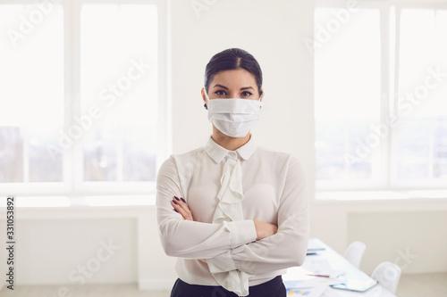 Obraz Danger of infection of the virus coronavirus infection. Businesswoman in medical mask at office - fototapety do salonu