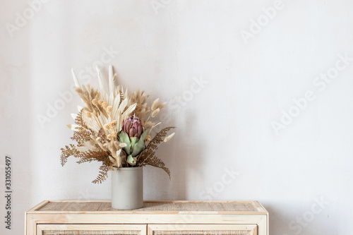 Minimalistic composition of dried flowers in cylindrical ceramic vase as home decoration.