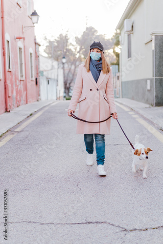 Fototapeta caucasian woman in the street wearing protective mask and walking with her dog. corona virus concept obraz