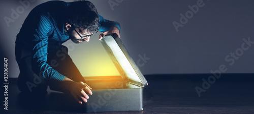 Obraz man open gift box on dark background - fototapety do salonu