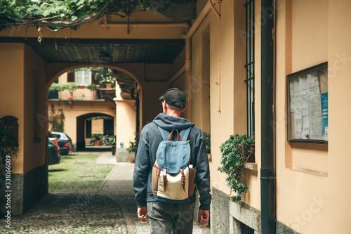A tourist or traveler with a backpack is looking for accommodation that he has booked or a student returned home after studying or on vacation Wallpaper Mural