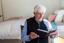 Senior Man Reading A Book In H...