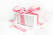 Leinwandbild Motiv White gift box with pink ribbon and a small pink hearts on white background. Selective focus. Copy space