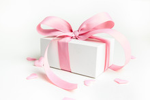 White Gift Box With Pink Ribbon And A Small Pink Hearts On White Background. Selective Focus. Copy Space