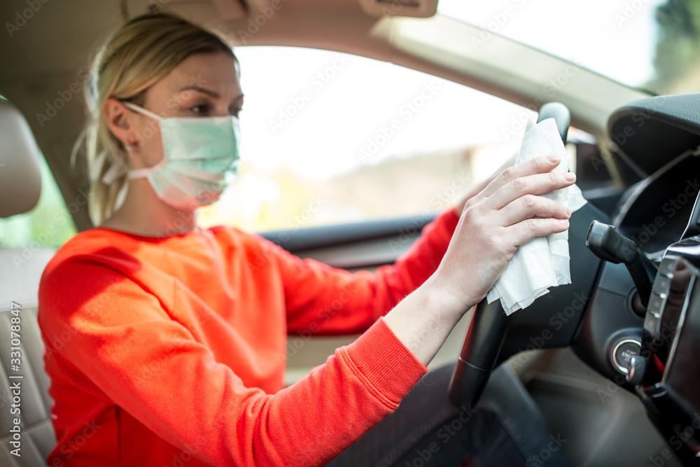 Fototapeta Epidemic outbreak. Woman cleaning steering wheel in the car.