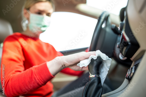 Epidemic outbreak. Woman cleaning steering wheel in the car. - 331078827