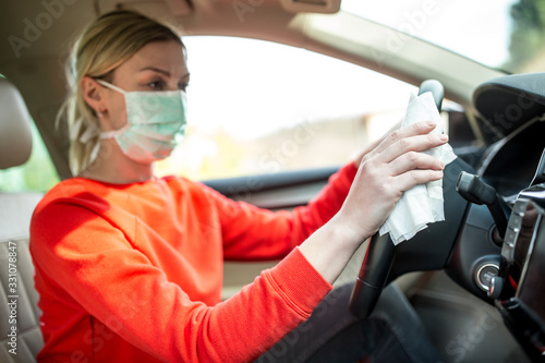 Obraz Epidemic outbreak. Woman cleaning steering wheel in the car. - fototapety do salonu