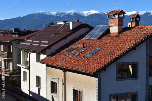 Fototapeta Breathtaking snowy mountain views over tiled rooftops of stone houses lined up a
