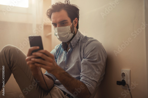 Single attractive man with a protective mask typing a message at home Fototapete