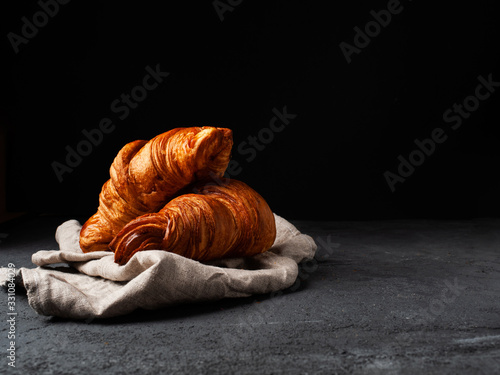 Fototapeta two golden croissants on a linen cloth on a dark background with free text space obraz