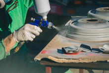 Man With Automotive Air Spray Gun In Action During The Restoration Of A Vintage Car. Applying First Base Layer Of Paint Onto Used Drum Brakes.