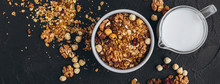 A Delicious And Crunchy Oatmeal Granola With Honey, Nuts, Dried Fruits And Grains Is Poured Out Of The Praml Package Into A Plate.  Food Photography Background