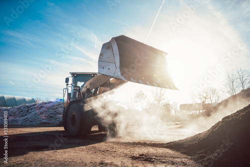 Bulldozer putting biomass on pile for composting Canvas Print