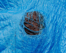 Close Up Worn Blue Tarp With Tattered Hole In Center,Fishing Nets