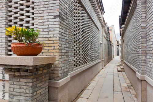 Fototapeta A characteristic alley of the retro style Chinese village, with brick houses and flagstone pavement, flower on pot decorated in entrance, Fuzhou,Fujian,China obraz