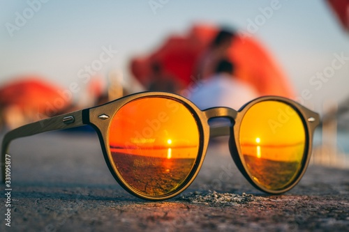 Fotografiet Pair of sunglasses on the beach with the reflection of the sunset