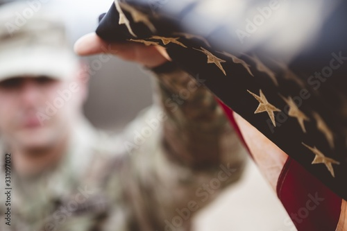Fotomural Shallow focus shot of an American soldier holding the American flag