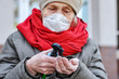 An elderly woman in a respirator handles her hands with a sanitizer antiseptic against coronavirus. COVID-2019 Senior Health. Old woman in a protective mask