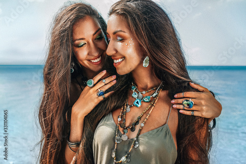 Fototapeta close up of two cheerful young women sisters twins on the beach obraz