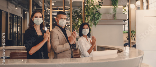 Vászonkép hotel receptionist wearing medical mask and show greeting with thai wai for bein