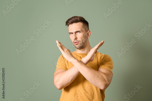 Fototapety, obrazy: Indignant man showing stop gesture on color background