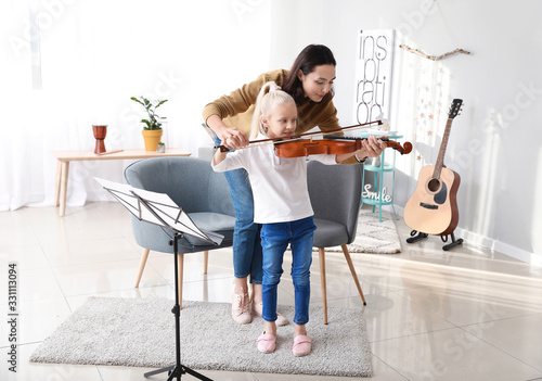 Fotomural Private music teacher giving violin lessons to little girl at home