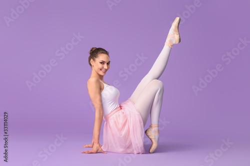 Fototapeta Beautiful young ballerina on color background