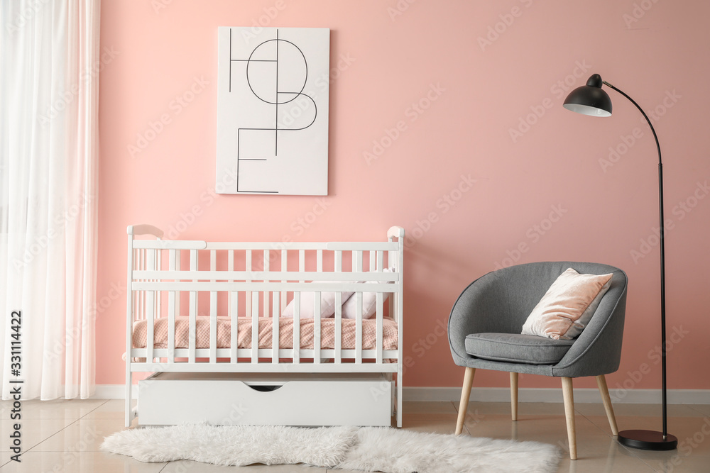 Fototapeta Baby bed with armchair in interior of children's room