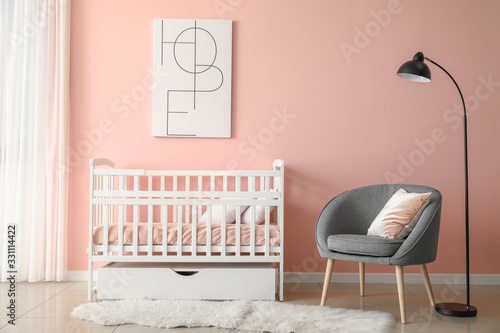 Baby bed with armchair in interior of children's room Canvas Print